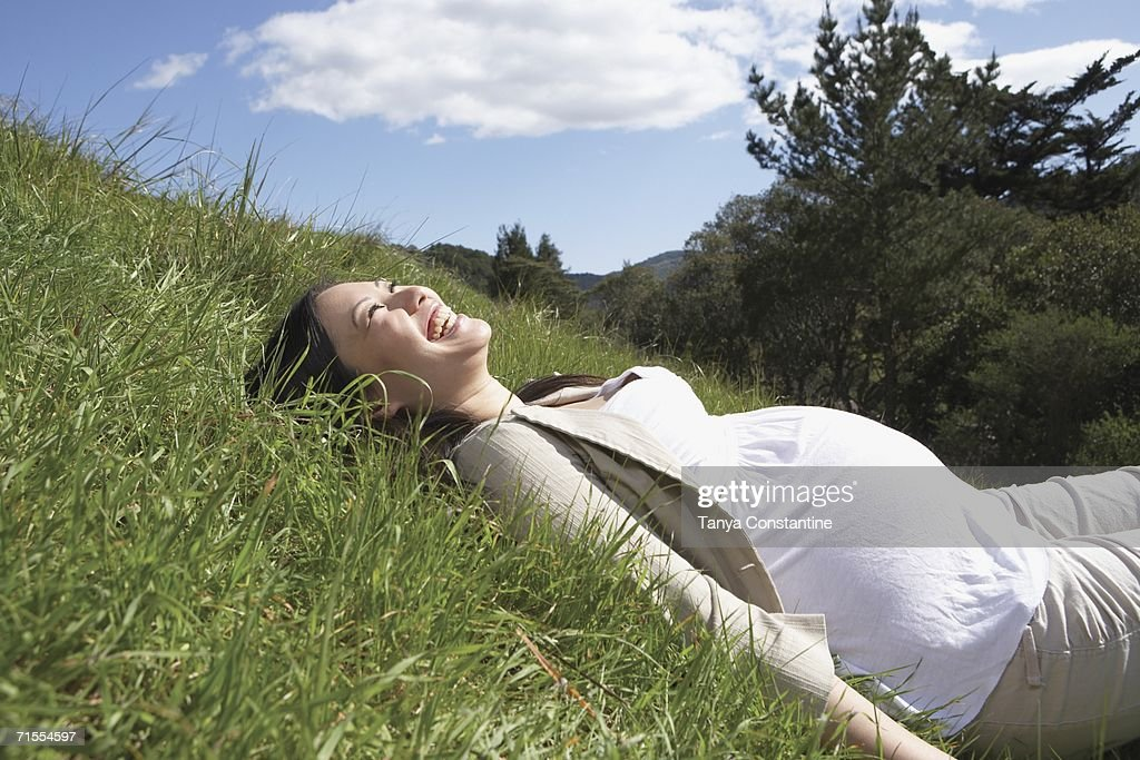 Pregnant Asian woman laying in the grass : Stock Photo