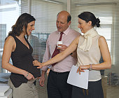 Pregnant businesswoman by colleagues in office