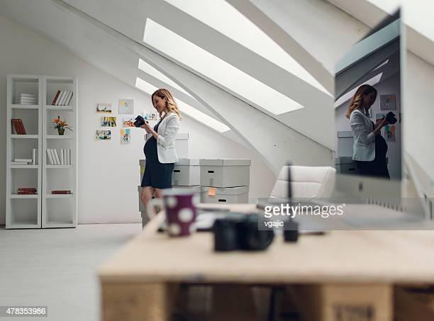 Schwanger Geschäftsfrau Holding Digitalkamera und arbeiten In Ihrem Büro.