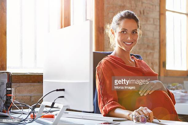 Pregnant businesswoman sitting at computer desk
