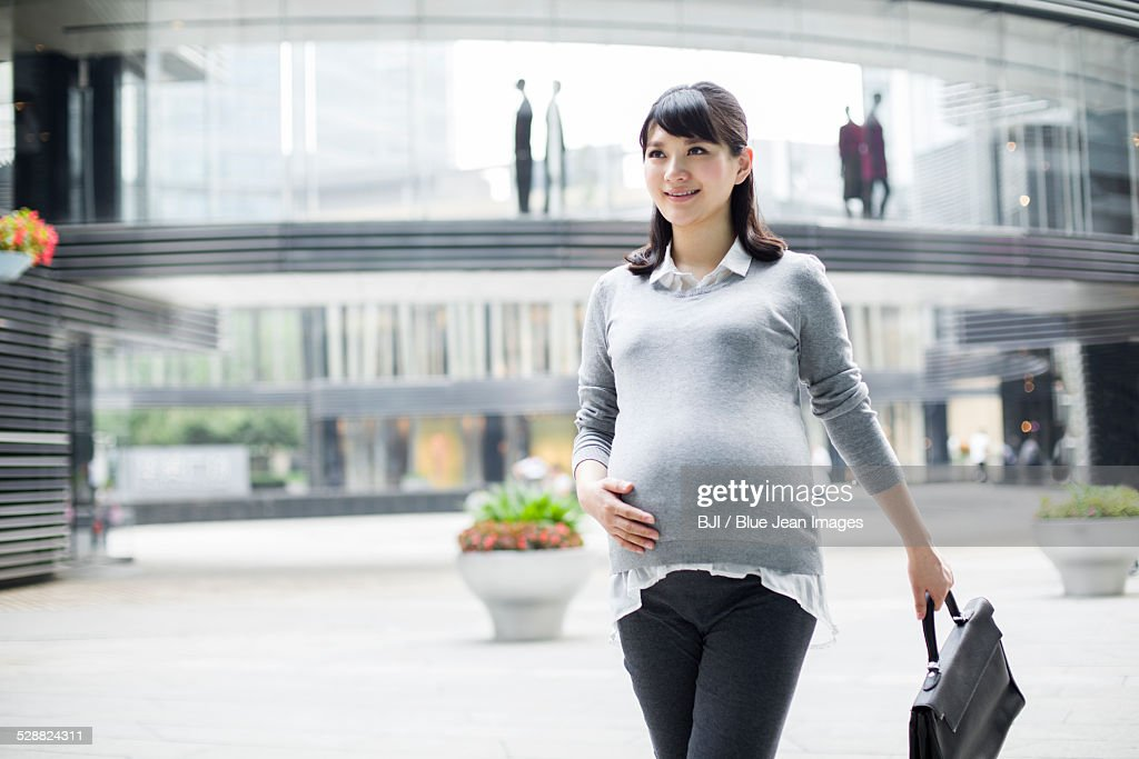 Pregnant businesswoman walking in city center : Stock Photo