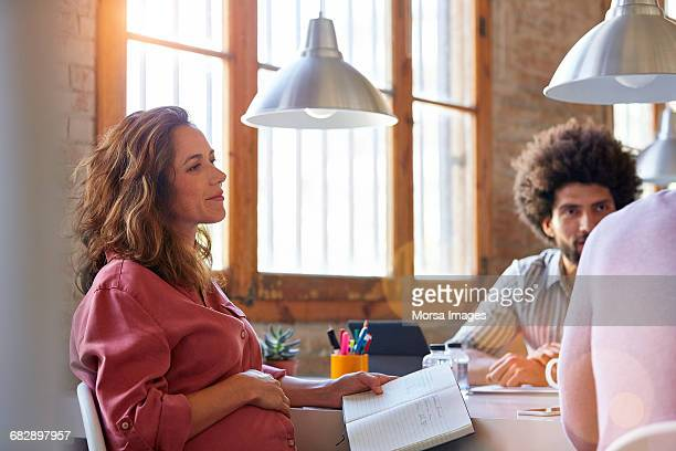 Pregnant businesswoman with colleagues in office