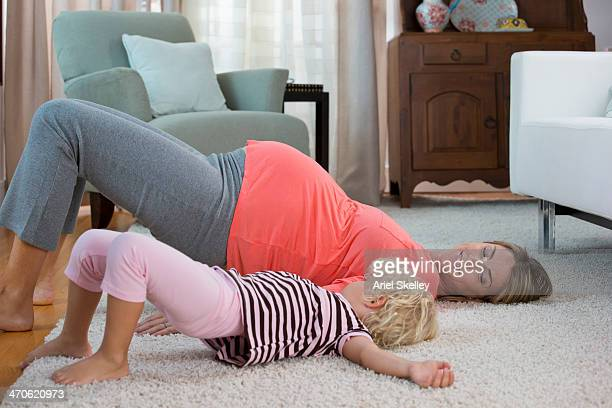 Pregnant Caucasian mother and daughter practicing yoga