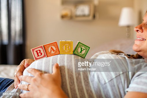 Pregnant Caucasian woman balancing wooden blocks on her stomach in bed : Stock Photo