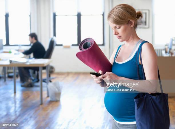 Pregnant Caucasian woman carrying yoga mat in office