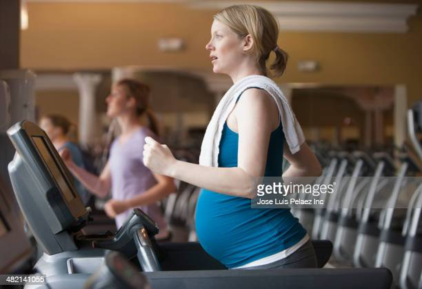 Pregnant Caucasian woman exercising on treadmill in gym