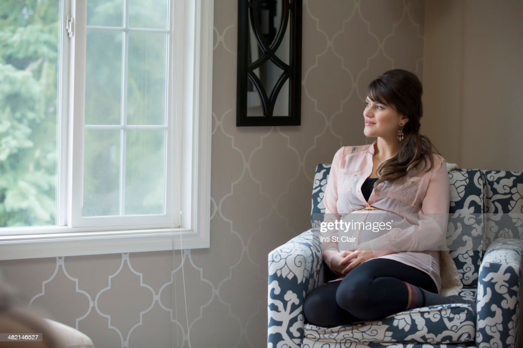 Pregnant Caucasian woman sitting in living room