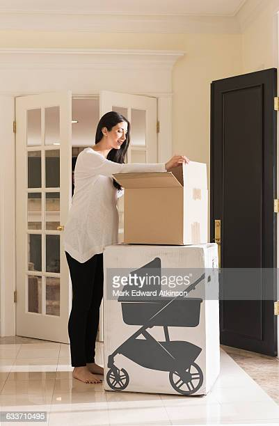 Pregnant Caucasian woman unpacking baby supplies