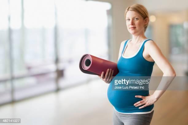 Pregnant Caucasian woman with mat in yoga studio
