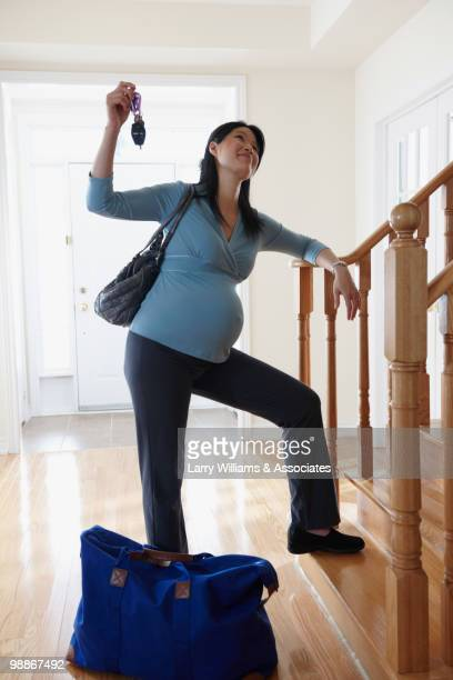 Pregnant Chinese woman with car keys and bag ready for hospital