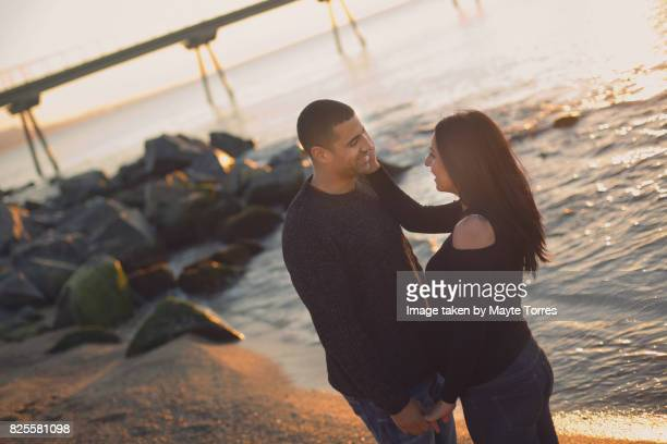 pregnant couple at the beach looking at each other