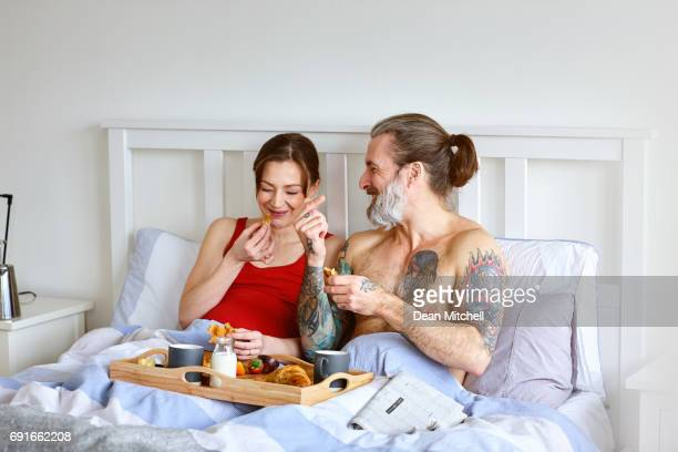 Pregnant couple enjoying breakfast in bed