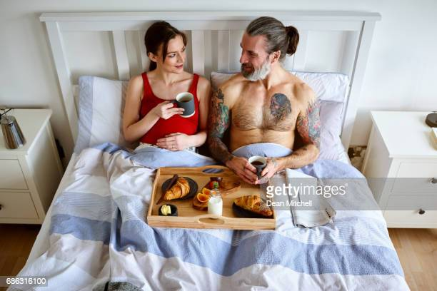 Pregnant couple having bed tea and breakfast