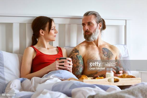 Pregnant couple having bed tea and discussing