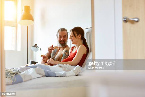 Pregnant couple having breakfast and smiling in bedroom
