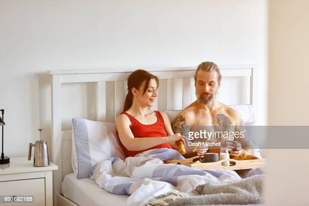 Pregnant couple having breakfast in bed