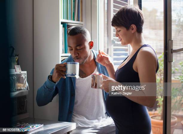 Pregnant couple having tea together in kitchen