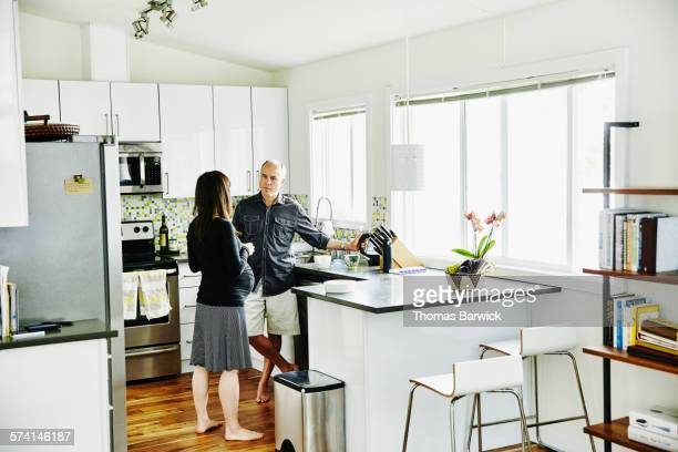 Pregnant couple in home kitchen making tea