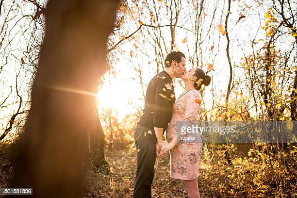 Pregnant couple in love in autumn