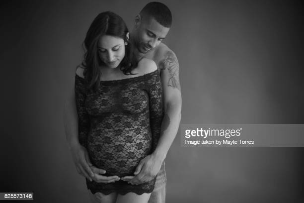 Pregnant couple in studio looking at belly