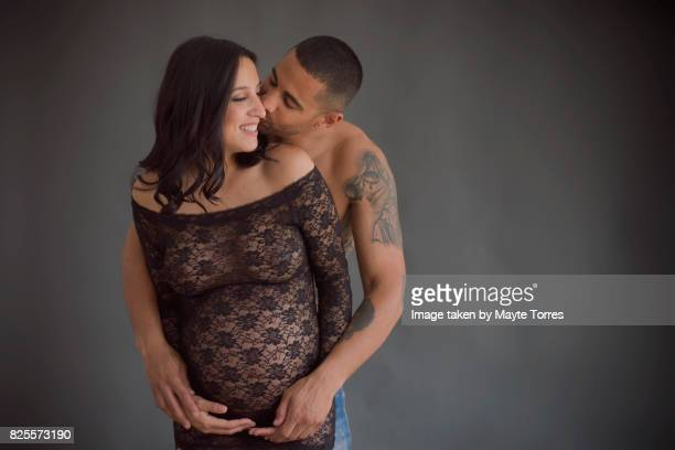 Pregnant couple in studio wearing lace