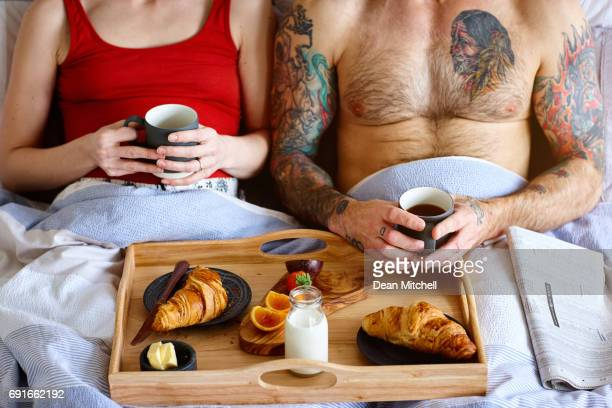 Pregnant couple sitting in bed and having breakfast