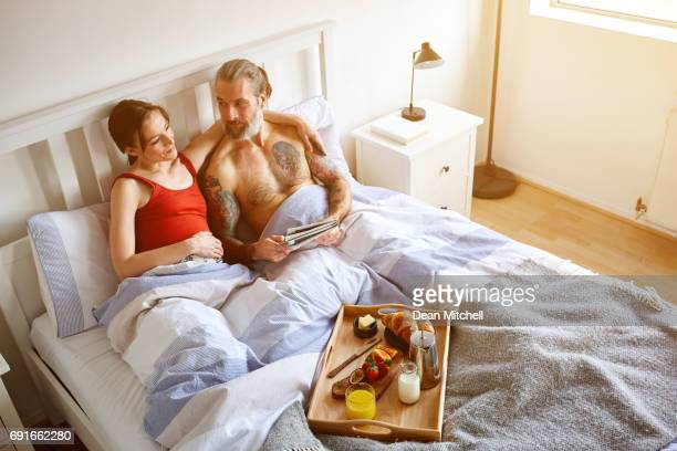 Pregnant couple sitting on bed in morning