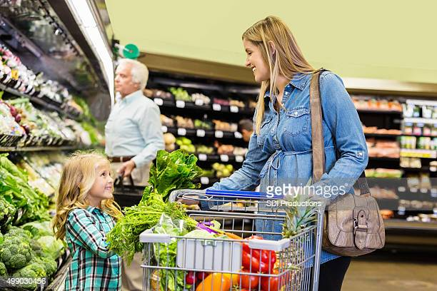 Pregnant customer shopping for groceries with daughter in supermarket