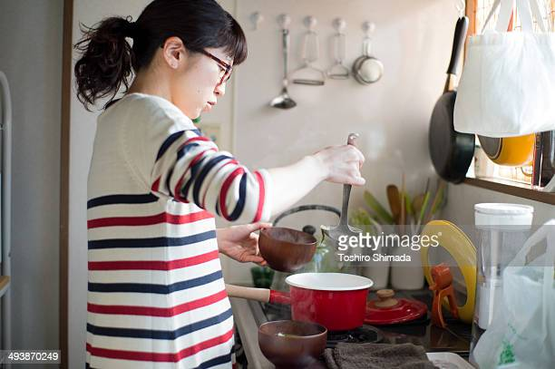 A pregnant female cooking in the kitchen