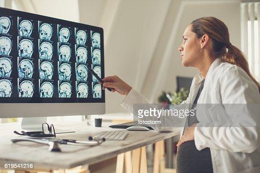 Pregnant female doctor examining brain scan