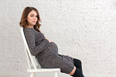 Pregnant female wearing grey dress sitting on a chair posing on white brickwall background.