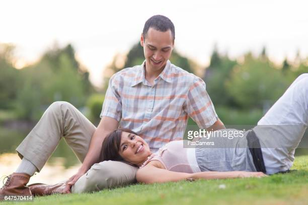 Pregnant Hawaiian Couple Relaxing in Park Outdoors