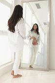 Pregnant Hispanic woman admiring her belly