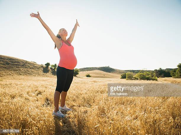 Pregnant Hispanic woman cheering in rural landscape