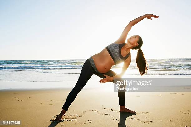 Pregnant Hispanic woman practicing yoga on beach