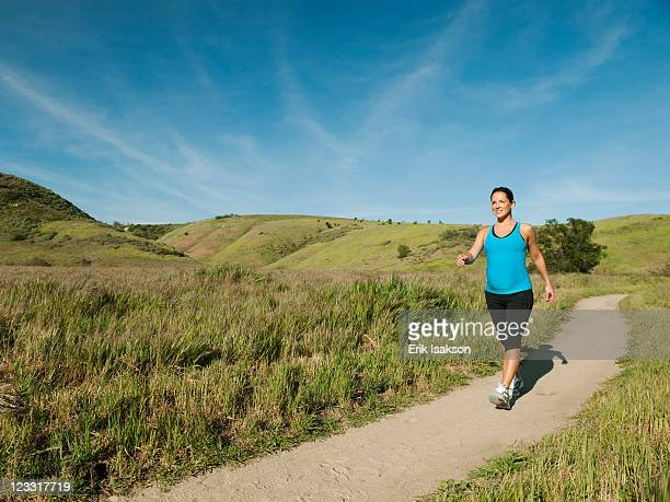 Pregnant Hispanic woman running in remote area