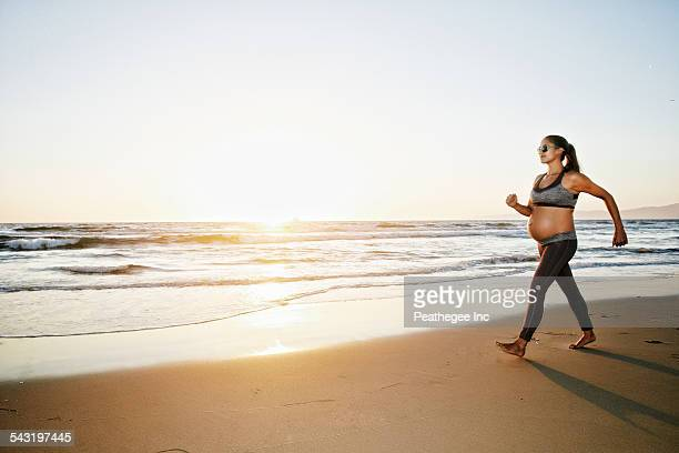 Pregnant Hispanic woman walking on beach
