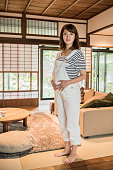 Pregnant Japanese woman wearing dungarees living room
