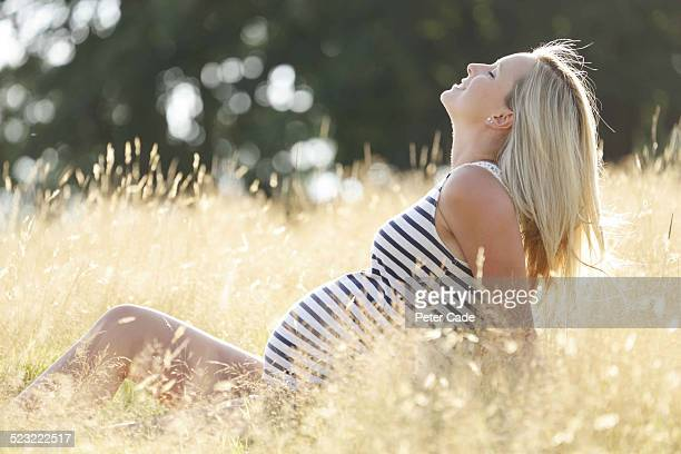 pregnant lady enjoying the sunshine in a field .