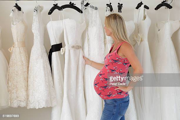 Pregnant lady looking at wedding dresses.