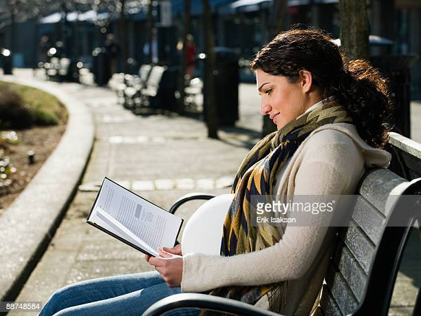 Pregnant Middle Eastern woman reading on park bench