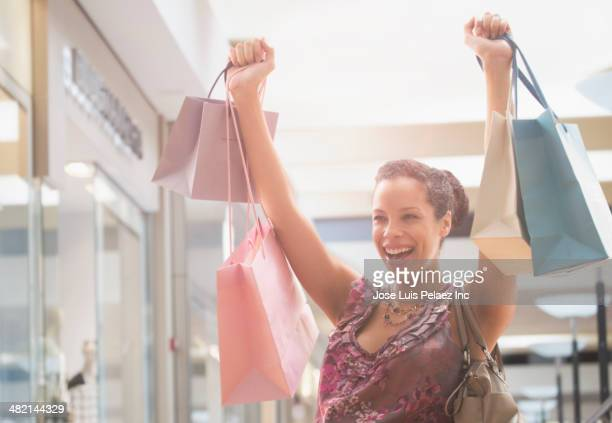 Pregnant mixed race woman cheering with shopping bags
