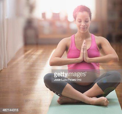 Pregnant mixed race woman meditating on yoga mat