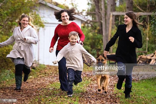 Femme enceinte mère, amis, petit garçon et chien jouant courir en automne