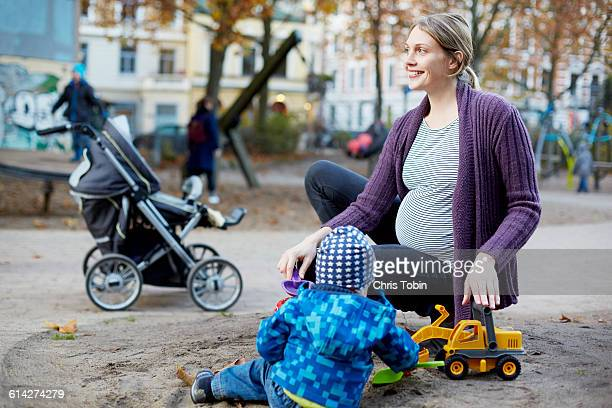 Pregnant mom playing with toddler on playground