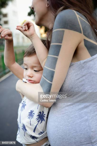 Pregnant mom trying to hold on to grumpy toddler