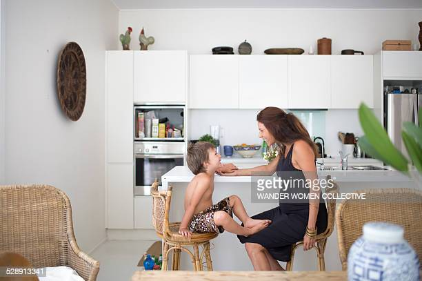 Pregnant mother and child at home in kitchen