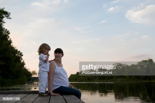 Pregnant Mother And Daughter Sitting On Jetty : Stock Photo