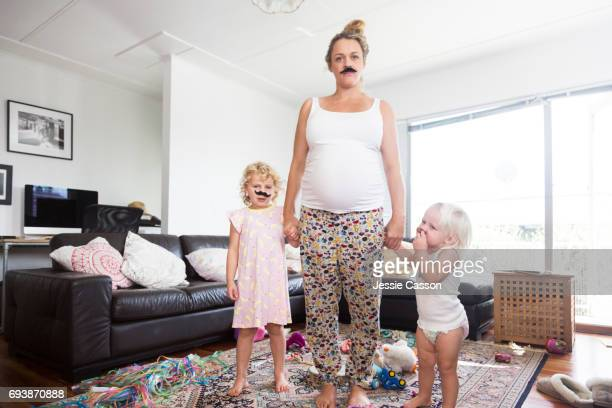 Pregnant mother and two children wearing moustaches in messy living room