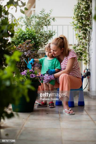 Pregnant mother gardening with her 2 year old boy